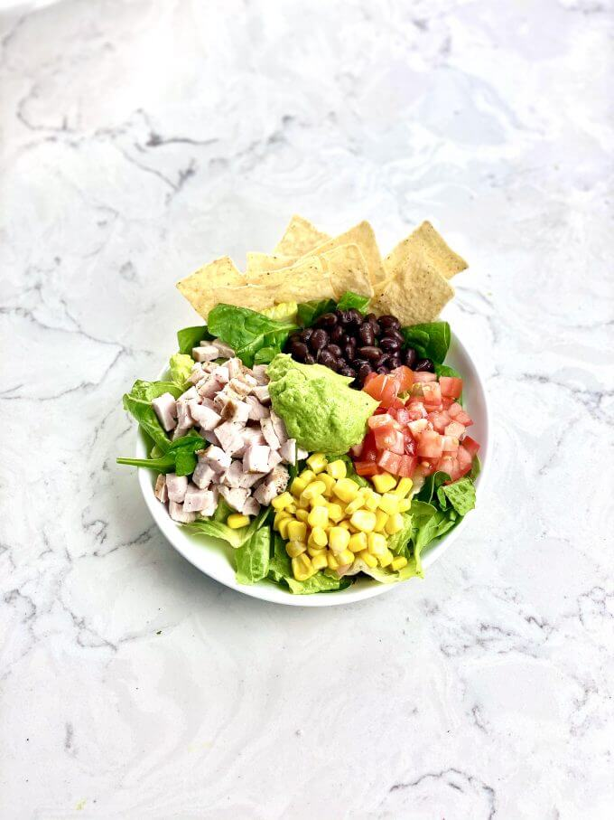 Bowl of Southwest Chicken Salad with avocado salad dressing recipe on top
