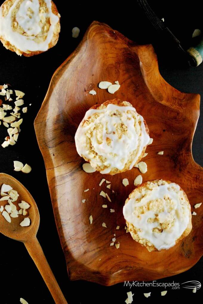 Overhead shot of two almond streusel muffins on a wooden plate