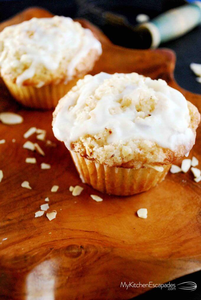 Two almond streusel muffins on a wooden plate