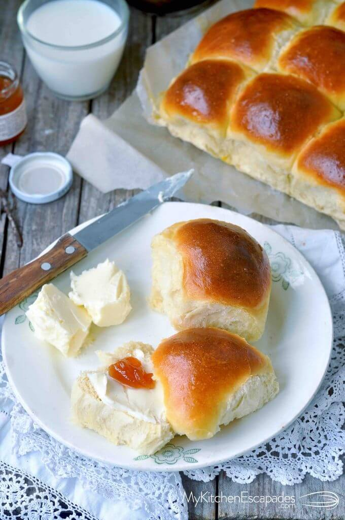 Two Hawaiian sweet rolls on a plate with butter