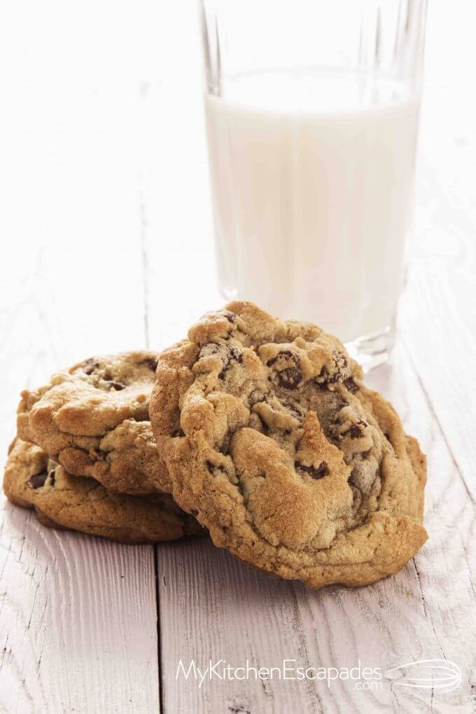 two chocolate chip cookies with a glass of milk