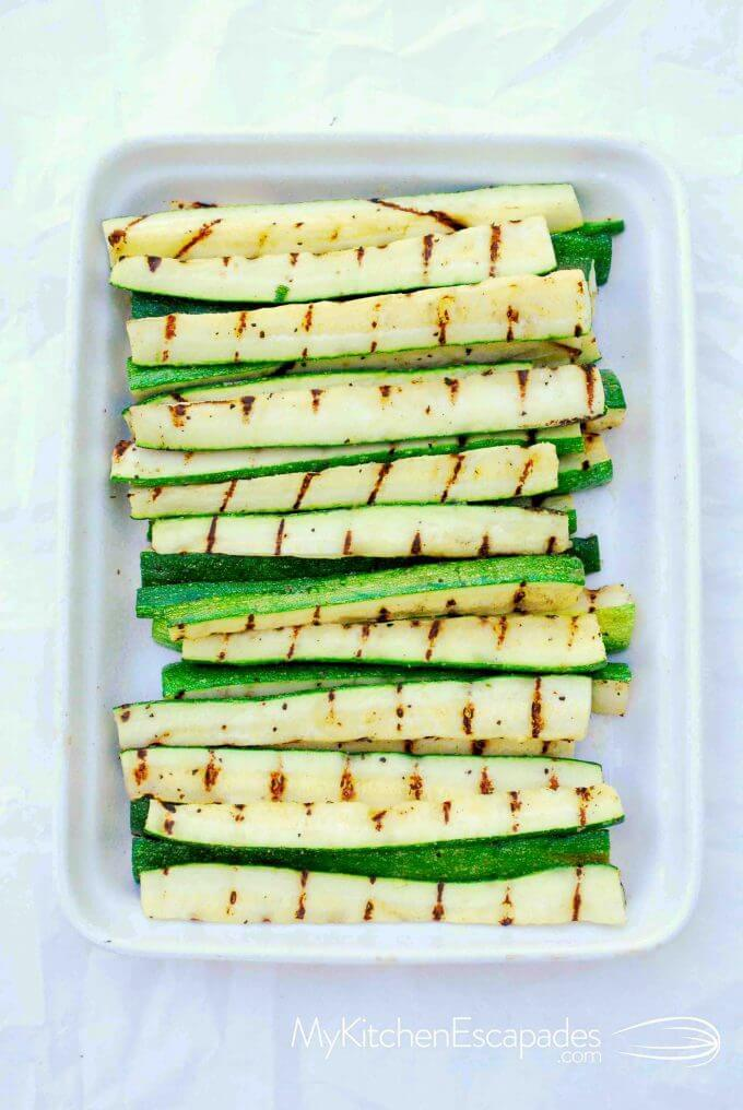 white dish of grilled zucchini spears