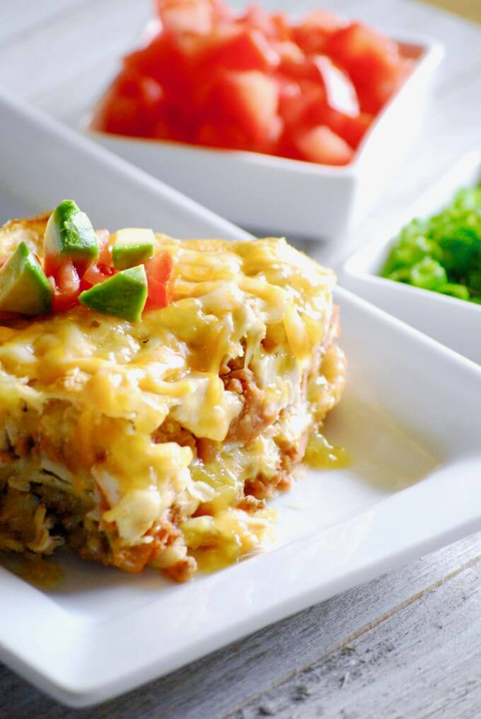 layered green chile chicken enchilada casserole with diced tomatoes in the back