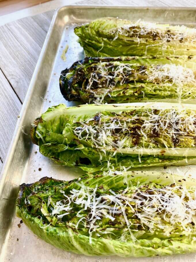 Pan of grilled romaine hearts with parmesan cheese sprinkled on top