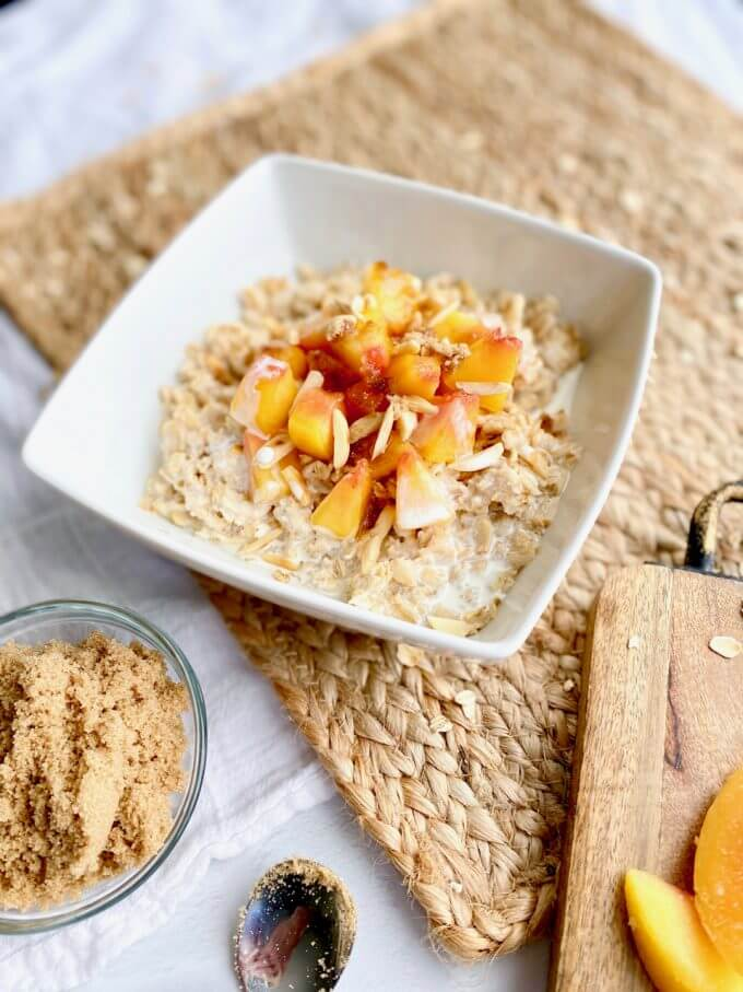 bowl of peach and cream oatmeal recipe with brown sugar on top