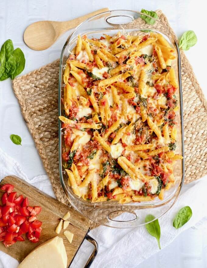 glass pan of penne pasta, spinach, tomatoes, and mozzarella cheese