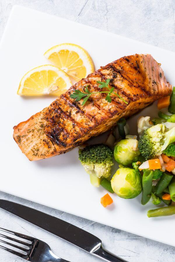 healthy grilled salmon on a plate with veggies